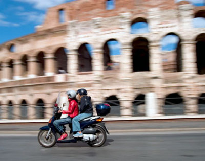 A motorcycle in front of the Coliseum in Rome
